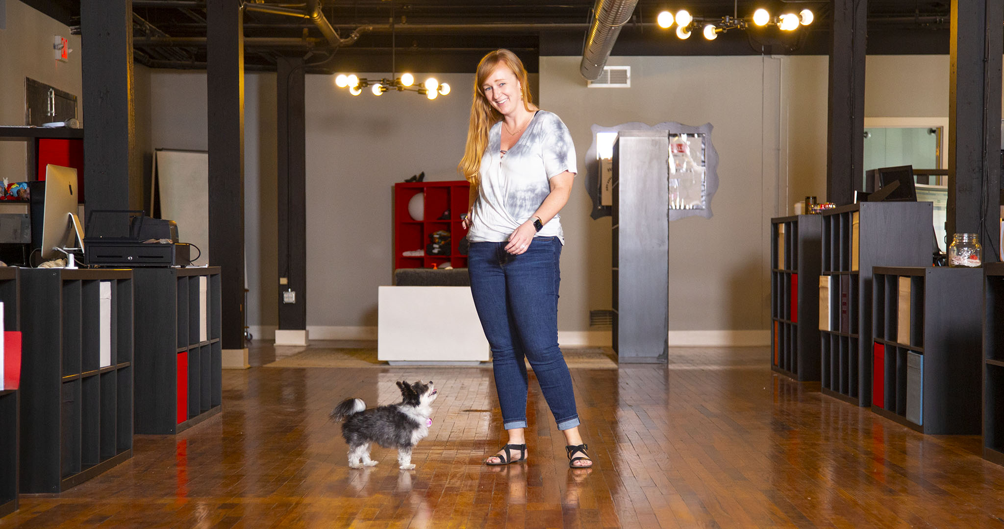 wide shot of Alicia Anderson standing in the middle of the office with her small black and white dog at her feet