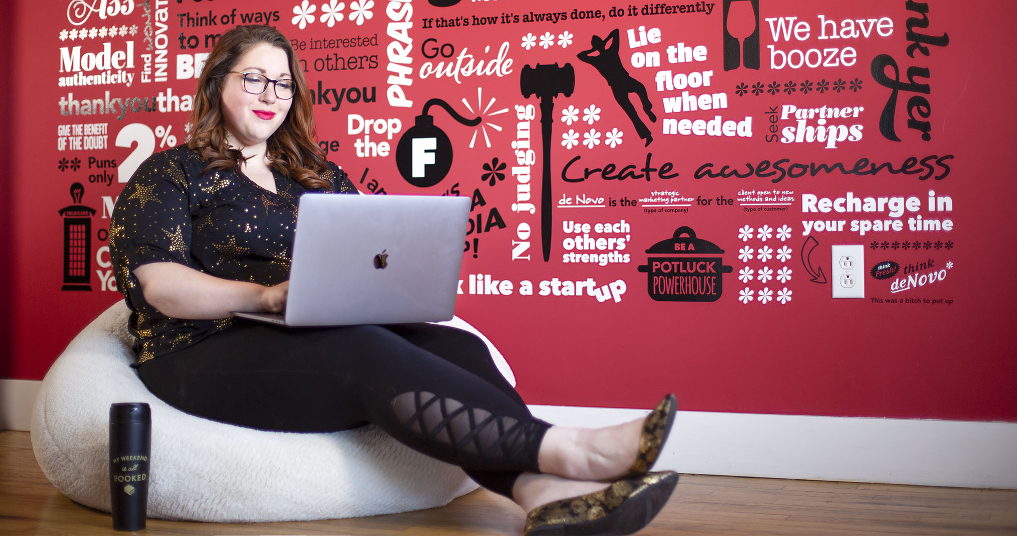 wide shot of Ally Machala sitting on a beanbag smiling at her laptop in her lap