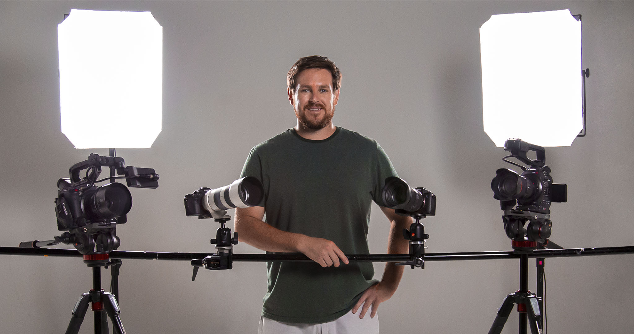 wide shot of Andrew Ravera standing behind a camera slider and multiple cameras